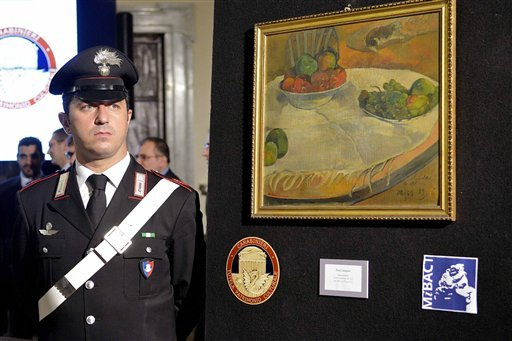 A carabiniere (Italian paramilitary police) officer stands by a Paul Gauguin still life recovered by authorities, during a press conference in Rome, Wednesday, April 2, 2014. (AP)
