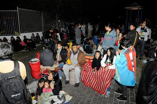 People sit outside as they evacuate their homes after a strong aftershock in Iquique, Chile, early Thursday, April 3, 2014. (AP Photo/Cristian Vivero)