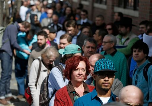 In this Thursday March 13, 2014, file photo, job seekers line up to attend a marijuana industry job far in Downtown Denver. The government issues the March jobs report on Friday, April 4, 2014. (AP Photo/Brennan Linsley, File)