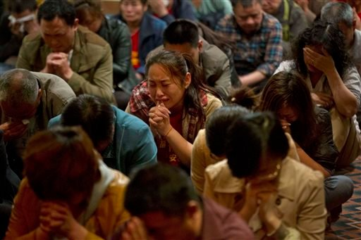 Relatives of Chinese passengers onboard the missing Malaysia Airlines plane, Flight MH370, cry as they pray in a prayer room in Beijing, China, Friday, April 4, 2014.