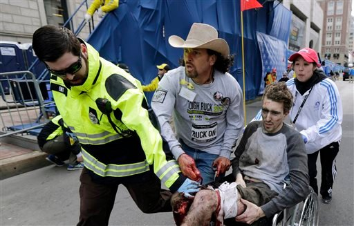 In this April 15, 2013 file photo, an emergency responder and volunteers, including Carlos Arredondo in the cowboy hat, push Jeff Bauman in a wheel chair after he was injured in an explosion near the finish line of the Boston Marathon in Boston.