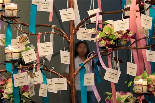 Well-wishes cards for passengers aboard the missing Malaysia Airlines Flight MH370 are tied during a mass prayer for the plane, in Kuala Lumpur, Malaysia, Sunday, April 6, 2014.