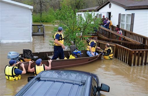 Firefighters rescue a family from their home, surrounded by floodwaters, in a mobile home park in Pelham, Ala., on Monday, April 7, 2014. Overnight storms dumped torrential rains in central Alabama, causing flooding across a wide area.