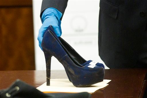 Prosecutor John Jordan sets down a stiletto shoe entered into evidence during the trial against Ana Lilia Trujillo Tuesday, April 1, 2014, in Houston.