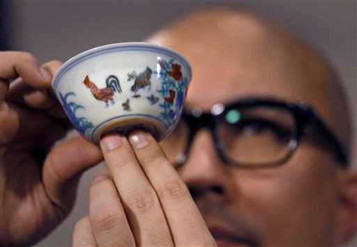 "Sotheby's Deputy Chairman for Asia Nicholas Chow presents the Meiyintang ""Chicken Cup"" from the Chinese Ming Dynasty (1368-1644) during a press conference in Hong Kong, Tuesday, April 8, 2014."