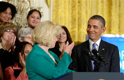 Lilly Ledbetter, center, applauds President Barack Obama, right, in the East Room of the White House in Washington, Tuesday, April 8, 2014, during an event marking Equal Pay Day. (AP Photo/Susan Walsh)