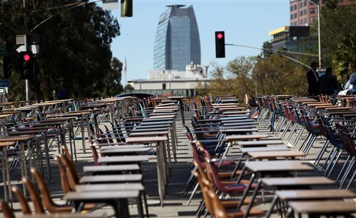 School desks placed by parents, district graduates and activists block a street in front of the Los Angeles Unified School District headquarters in a demonstration against student dropout rates Tuesday, April 8, 2014, in downtown Los Angeles. (AP)