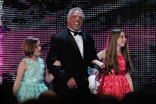 In this April 5, 2014 file photo provided by the WWE, James Hellwig, aka The Ultimate Warrior, is escorted by his daughters to the stage during the WWE Hall of Fame Induction at the Smoothie King Center in New Orleans.