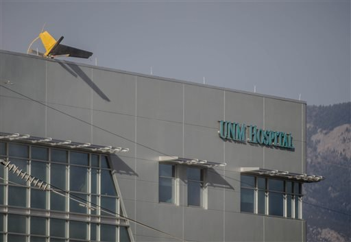 A helicopter's tail hangs over the edge of the UNM Hospital Wednesday afternoon, April 9, 2014, when it crashed as it took off from the roof of the building. (AP Photo/The Albuquerque Journal, Roberto E. Rosales)