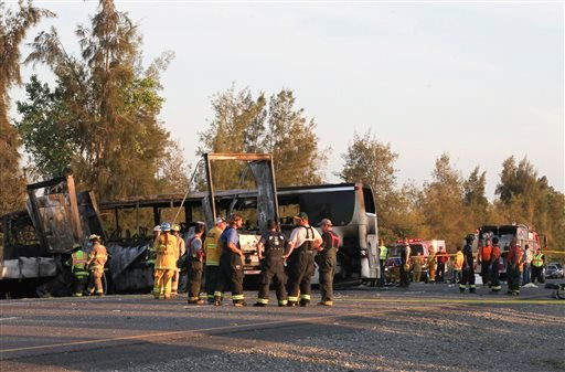 Rescue workers, police and firefighters work the scene where nine people were killed in a three-vehicle crash involving a bus carrying high school students on a visit to a college, Thursday, April 10, 2014, near Orland, Calif. (AP)