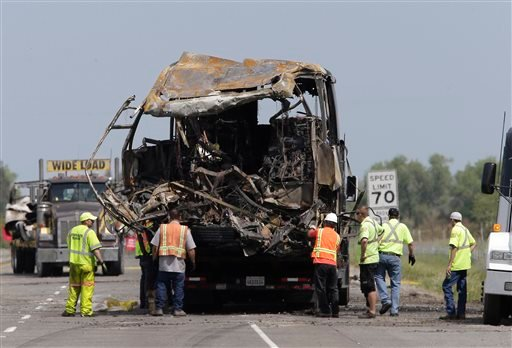 The burned out remains of a tour bus involved in a fiery crash with FedEx truck, sits on a flatbed truck before being taken from the scene, Friday April 11, 2014 in Orland, Calif.