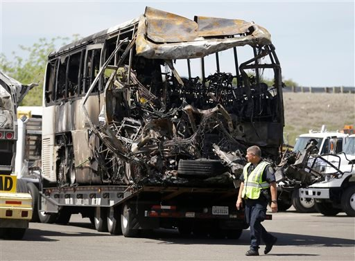 A California Highway Patrol officer walks past the charred remains of a tour bus at a CalTrans maintenance station in Willows, Calif., Friday, April 11, 2014.