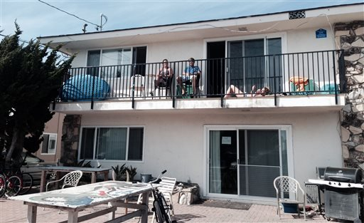 This Tuesday, April 8, 2014 photo shows JelenaTasic, Josh Elter and Jeanine Zolczynski, all seniors at UC Santa Barbara, resting on a balcony of a home in Isla Vista, Calif.