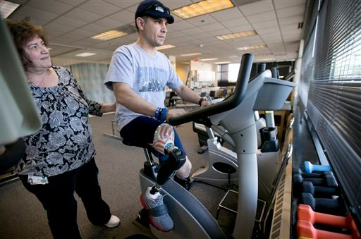 In this Thursday, April 3, 2014 photo, Boston Marathon bombing survivor Marc Fucarile, of Reading, Mass., right, is helped by physical therapy assistant Joy Ross.
