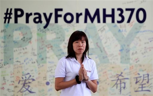 A member of Kechara Buddhist organization offers prayers for passengers onboard the missing Malaysia Airlines Flight 370 at Kechara Forest Retreat in Bentong, outside Kuala Lumpur, Malaysia, Sunday, April 13, 2014.