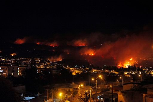 An out of control forest fire rages towards urban areas in the city of Valparaiso, Chile, Saturday, April 12, 2014. Authorities say the forest fire has destroyed at least 150 homes and is forcing evacuations. ( AP Photo/ Luis Hidalgo)