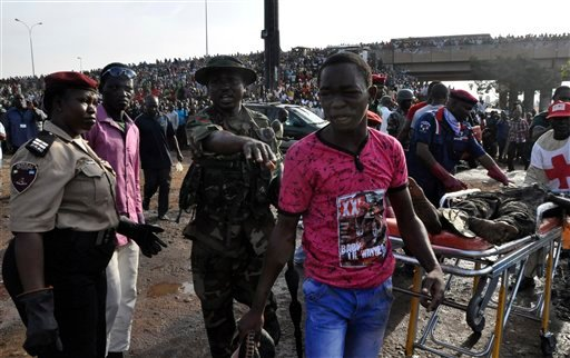 A man is directed by rescue workers as they collect the bodies of victims at the site of a blast at the Nyanya Motor Park, about 16 kilometers (10 miles) from the center of Abuja, Nigeria, Monday, April 14, 2014.(AP Photo/Gbemiga Olamikan)