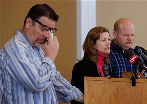Will Corporon, left, and Tony Corporon, right, fight emotions while Mindy Losen, center, talks about her son and father during a news conference at their church in Leawood, Kan., Monday, April 14, 2014.