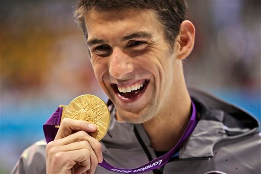 In this Aug. 3, 2012, file photo, United States' Michael Phelps displays his gold medal for the men's 100-meter butterfly swimming final at the Aquatics Centre in the Olympic Park during the 2012 Summer Olympics in London.