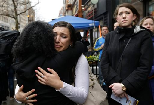 Olivia Savarino, center, hugs Christelle Pierre-Louis, left, as Callie Benjamin, right, looks on near the finish line of the Boston Marathon during ceremonies on Boylston Street, Tuesday, April 15, 2014, in Boston.