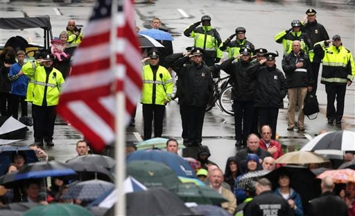 Police salute as a U.S. flag is raised at the finish line during a tribute in honor of the one year anniversary of the Boston Marathon bombings, Tuesday, April 15, 2014 in Boston. (AP Photo/Charles Krupa)