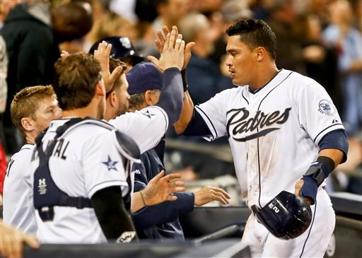 San Diego Padres' Everth Cabrera is congratulated at the dugout after his run producing double and then scoring against the Colorado Rockies in the fifth inning of a baseball game Monday, April 14, 2014, in San Diego. (AP Photo/Lenny Ignelzi)