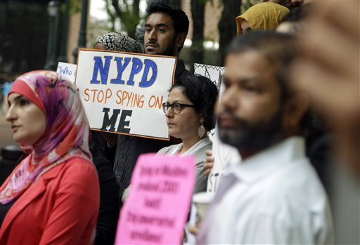 In this Aug. 28, 2014, file photo, a group of people hold signs protesting the New York Police Department's program of infiltrating and informing on Muslim communities during a rally near police headquarters in New York.
