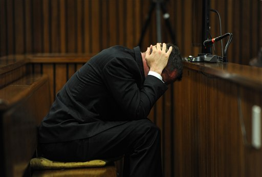 Oscar Pistorius reacts as he listens to forensic evidence being given in court in Pretoria, South Africa April 16, 2014. Pistorius is charged with the murder of his girlfriend, Reeva Steenkamp, on Valentines Day in 2013. (AP Photo/Werner Beukes, Pool)