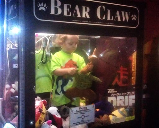 In this April 14, 2014 photo provided by Rachelle Hildreth, a 3-year-old boy plays with stuffed toys inside a claw crane game machine at a bowling alley in Lincoln, Neb. (AP)