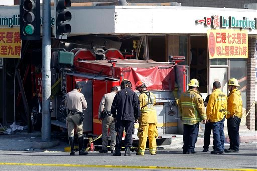 Firefighters and other officials work the scene of an accident where two firetrucks answering a call collided en route to a fire Wednesday, April 16, 2014, in Monterrey Park, Calif. (AP)