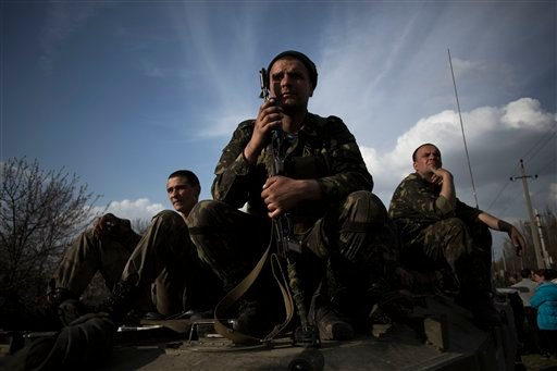 Soldiers of the Ukrainian Army sit atop combat vehicles as they are blocked by people on their way to the town of Kramatorsk on Wednesday, April 16, 2014. (AP Photo/Manu Brabo)