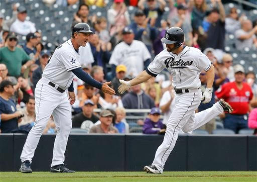 San Diego Padres' Xavier Nady is congratulated by third base coach Glenn Hoffman while rounding the bases on a solo home run against the Colorado Rockies during the fourth inning of a baseball game Thursday, April 17, 2014, in San Diego.