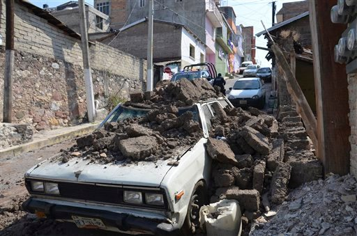 A parked car suffered damage when a adobe wall collapsed on it after a strong earthquake shook Chilpancingo, Mexico, Friday morning, April 18, 2014. (AP)