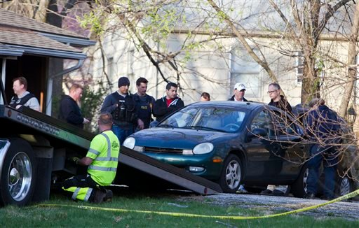 A car is removed by Kansas City police from the house, far right, of a Grandview man suspected in a series of shootings that have occurred on area roadways since early March, according to Police Chief Darryl Forté.