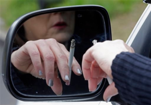 This March 2, file 2013 file photo shows a woman smoking a cigarette while sitting in her truck in Hayneville, Ala.