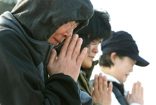 Relatives of passengers aboard the sunken ferry Sewol pray as they wait for their missing loved ones at a port in Jindo, South Korea, Monday, April 21, 2014.