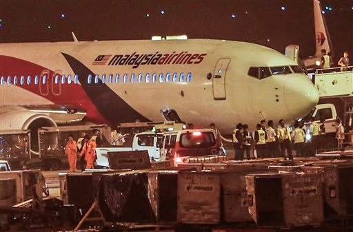 Ground crew check the Malaysia Airlines flight MH192 bound for Bangalore that turned back towards and parked at Kuala Lumpur International Airport in Sepang, Malaysia, Monday, April 21, 2014, after its right landing gear malfunctioned upon takeoff.