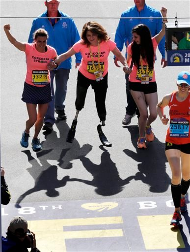 Double amputee Celeste Corcoran, center, a victim of last year's bombings, reaches the finish line of the 118th Boston Marathon.