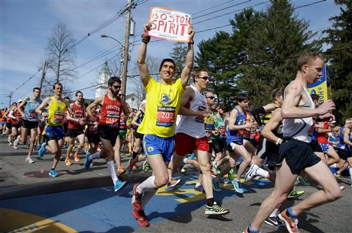 Runners in the first wave of 9,000 cross the start line of the 118th Boston Marathon Monday, April 21, 2014 in Hopkinton, Mass.