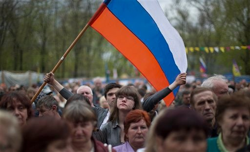 People wave a Russian national flag as they gather at barricades at the Ukrainian regional office of the Security Service in Luhansk, Ukraine, Monday, April 21, 2014. (AP)