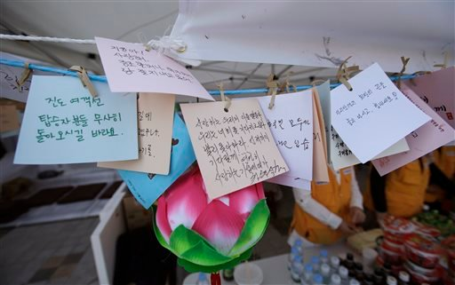 Messages wishing safe return of passengers aboard the sunken ferry Sewol hang with a Buddhism lotus decoration in Jindo, south of Seoul, South Korea, Tuesday, April 22, 2014.(AP Photo/Lee Jin-man)