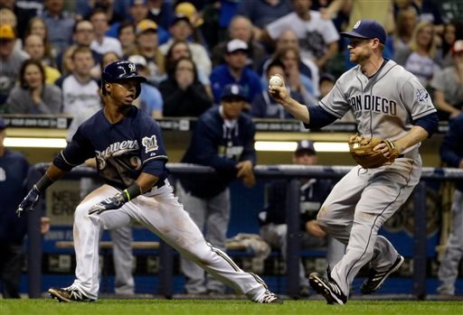 Milwaukee Brewers' Jean Segura is tagged out by San Diego Padres third baseman Chase Headley as he tries to score from third during the eighth inning of a baseball game Monday, April 21, 2014, in Milwaukee. (AP Photo/Morry Gash)