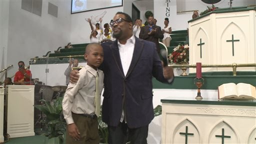 In an April 10, 2014, image provided by WXIA-TV, 9-year-old Willie Myrick is embraced by Grammy Award-winning gospel singer Hezekiah Walker in front of the congregation at Mt. Carmel Baptist Church in Atlanta. (AP)