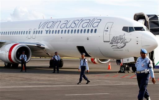 Indonesian Air Force personnel stand guard near a Virgin Australia airplane in Bali, Indonesia, Friday, April 25, 2014.
