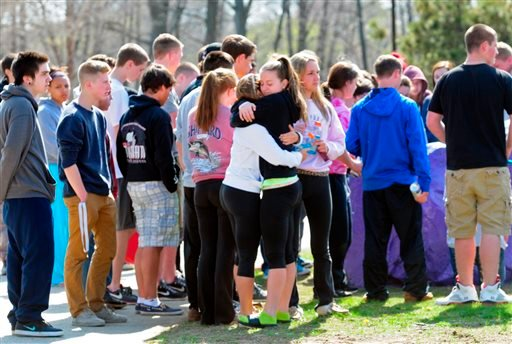 Students hug and spray paint a rock purple outside Jonathan Law High School in Milford, Conn., Friday, April 25, 2014, in memory of 16-year-old stabbing victim Maren Sanchez. (AP)