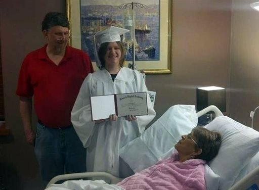 In this Monday, April 21, 2014 photo courtesy of Evie Shumaker, 17-year-old Evie Shumaker, of Newport, Ohio, displays her diploma after a special graduation ceremony in her mother's room at Licking Memorial Hospital in Newark, Ohio.