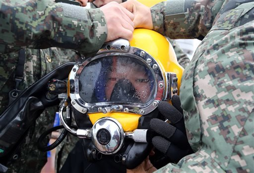 A diver wears a helmet to look for people still missing from the sunken ferry Sewol, in the water off the southern coast near Jindo, South Korea, Saturday, April 26, 2014.