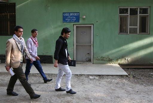 Afghan university students walk in front of health clinic at Kabul University where slain American John Gabel worked at Kabul University, teaching computer science classes in his spare time, in Kabul, Afghanistan, Saturday, April 26, 2014.