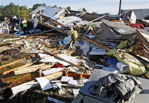 People stand among the remains of a mobile home Saturday, April 26, 2014, that was destroyed when a tornado touched down along Black Jack-Simpson Road in Greenville, N.C. on Friday, April 25, 2014.