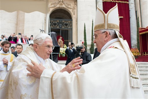 In this photo provided by the Vatican newspaper L'Osservatore Romano, Pope Francis, right, embraces his predecessor Pope Emeritus Benedict XVI, during a ceremony in St. Peter's Square at the Vatican, Sunday, April 27, 2014.